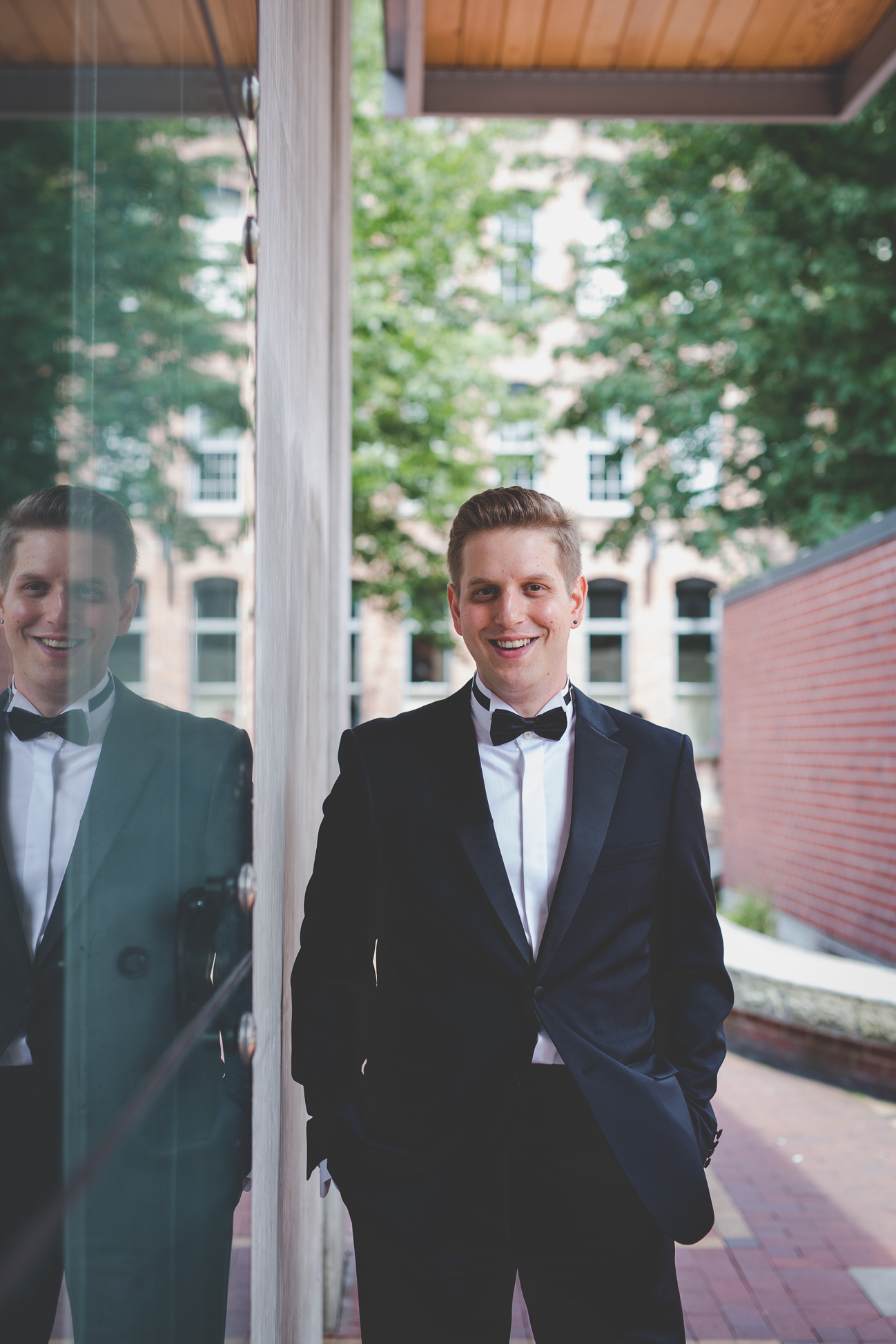 groom in black tuxedo and black bow tie standing next to window with reflection in glass