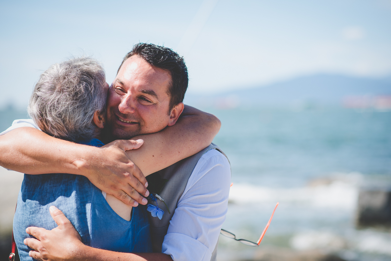 groom hugs mother in law after intimate elopement on Kits Beach