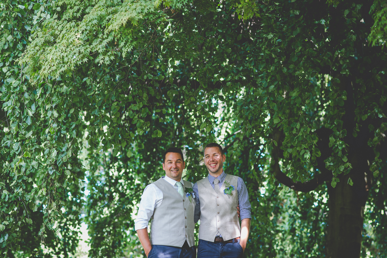 grooms laugh under a tree at Kitsilano Beach in Vancouver, BC