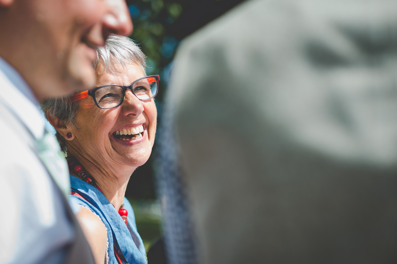 mother of the groom laughs during casual picnic reception at Kitsilano Beach elopement