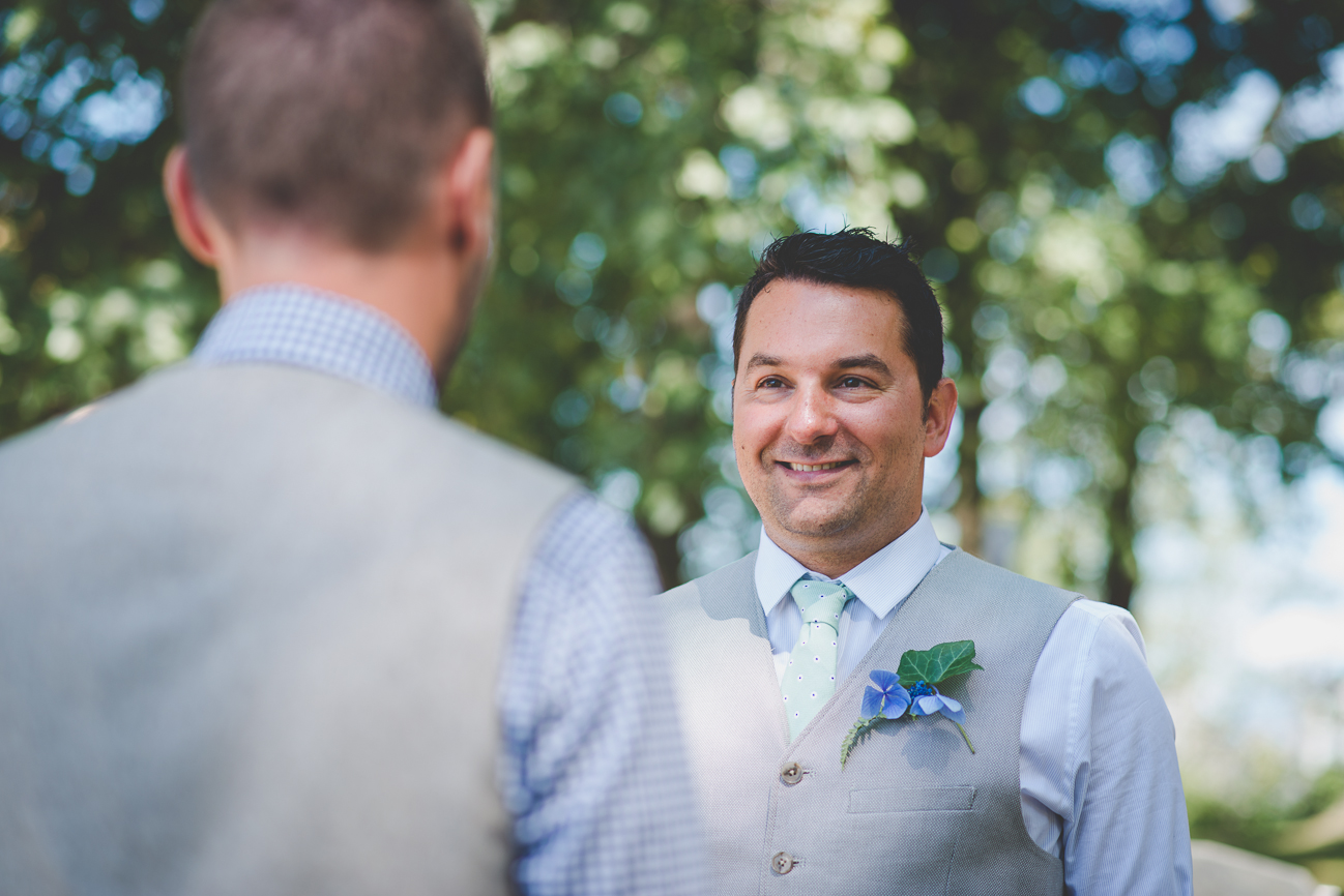 candid moment between grooms during portraits at same sex wedding in Vancouver, BC