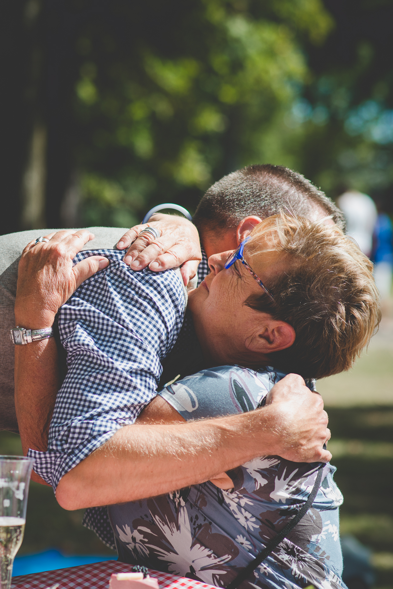 groom hugs mother-in-law after her speech at intimate beach picnic reception