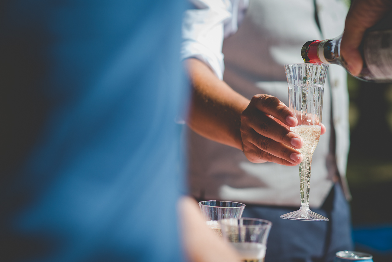 pouring champagne into plastic champagne glasses at intimate picnic beach elopement reception