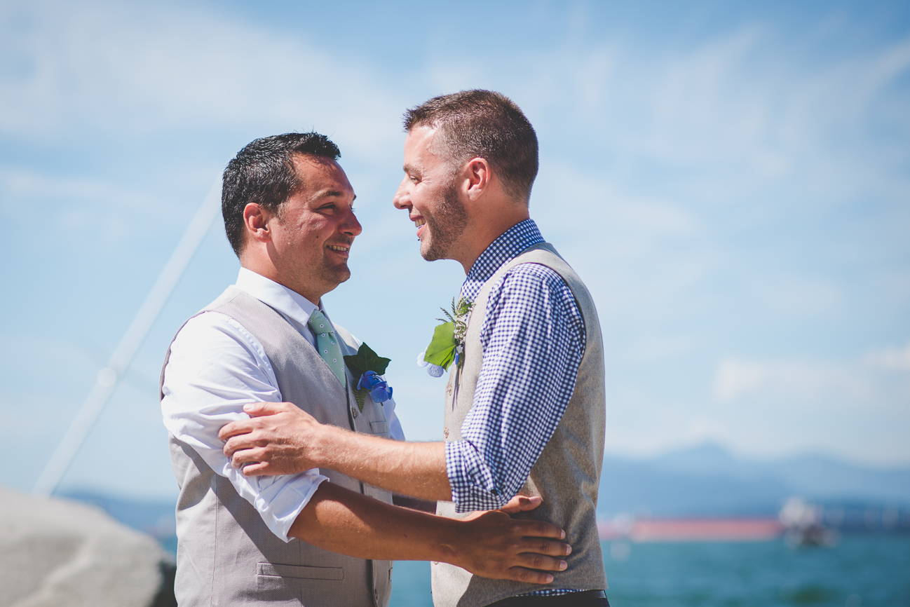 grooms hug and smile after first kiss at same sex elopement on the beach