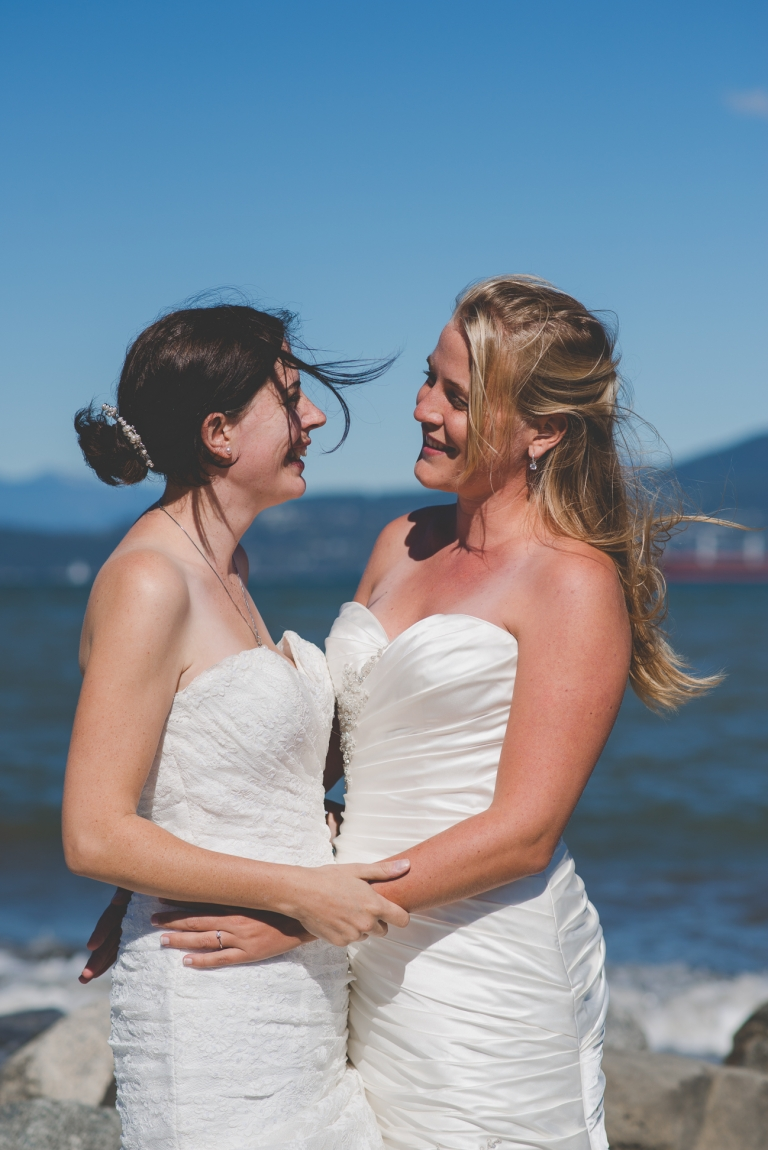 lesbian couple in wedding dresses laugh together while hair blows in the wind at Jericho Beach