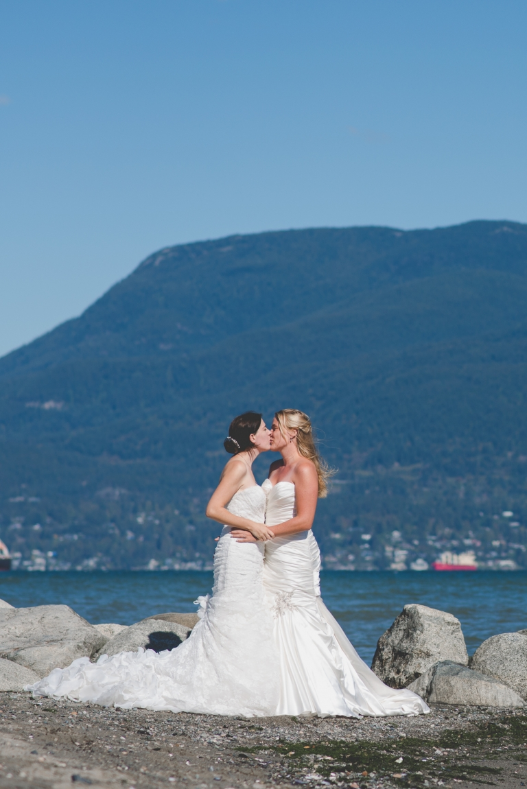 lesbian couple in wedding dresses kiss during wedding portraits on Jericho Beach in Vancouver
