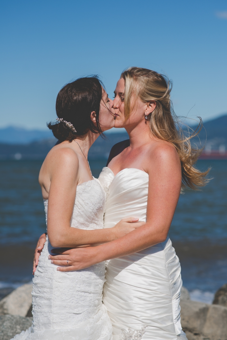 same sex couple kisses while hair blows in the wind at the beach during wedding portraits