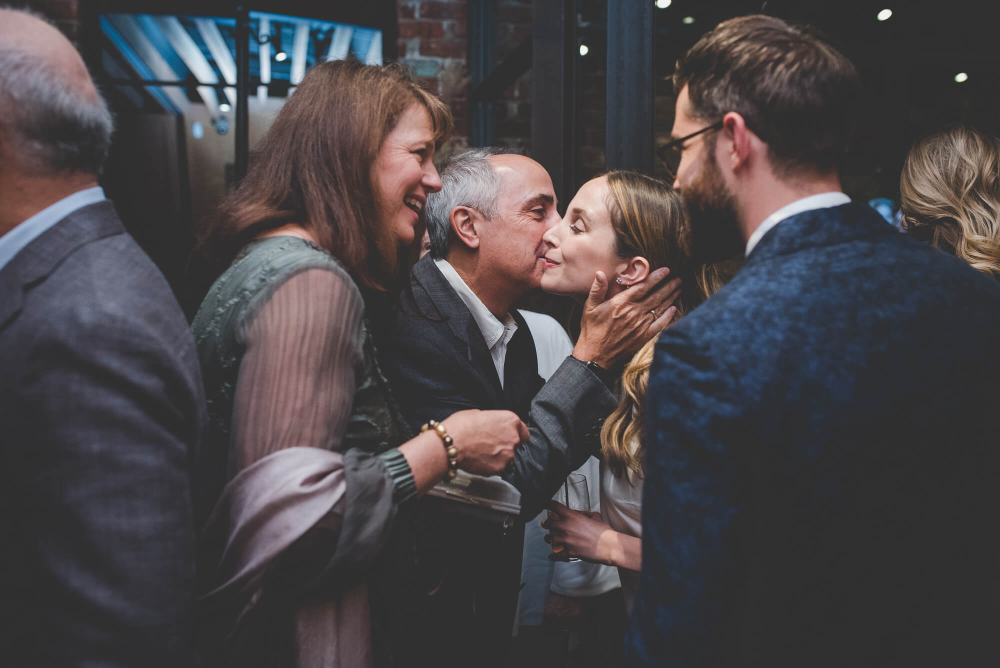 guest greeting bride with a kiss on the cheek at urban wedding reception in Vancouver