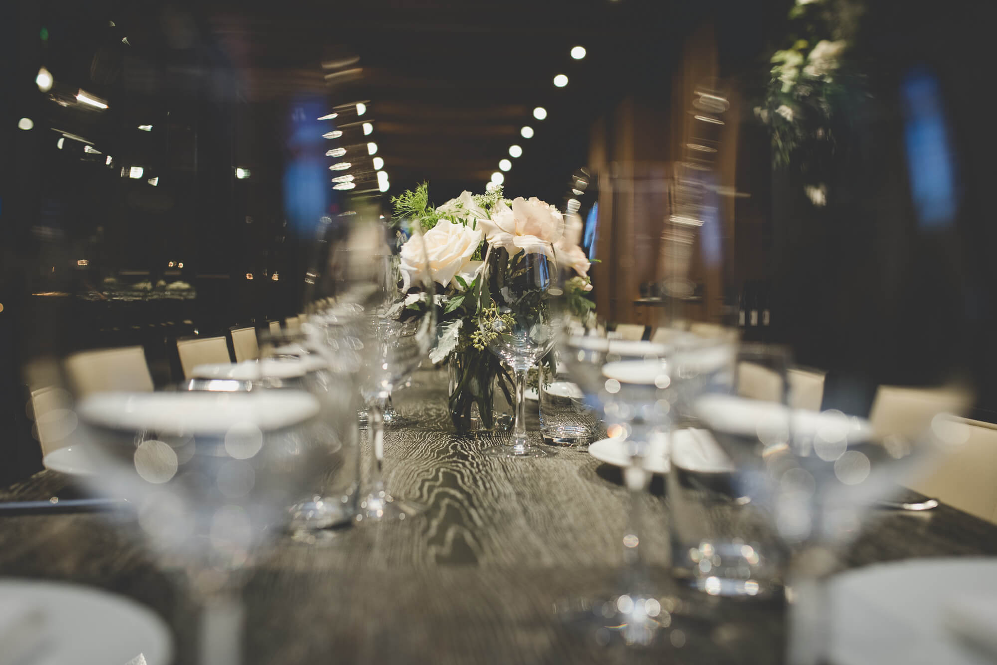 simple rose and green foliage centrepieces at intimate urban wedding reception