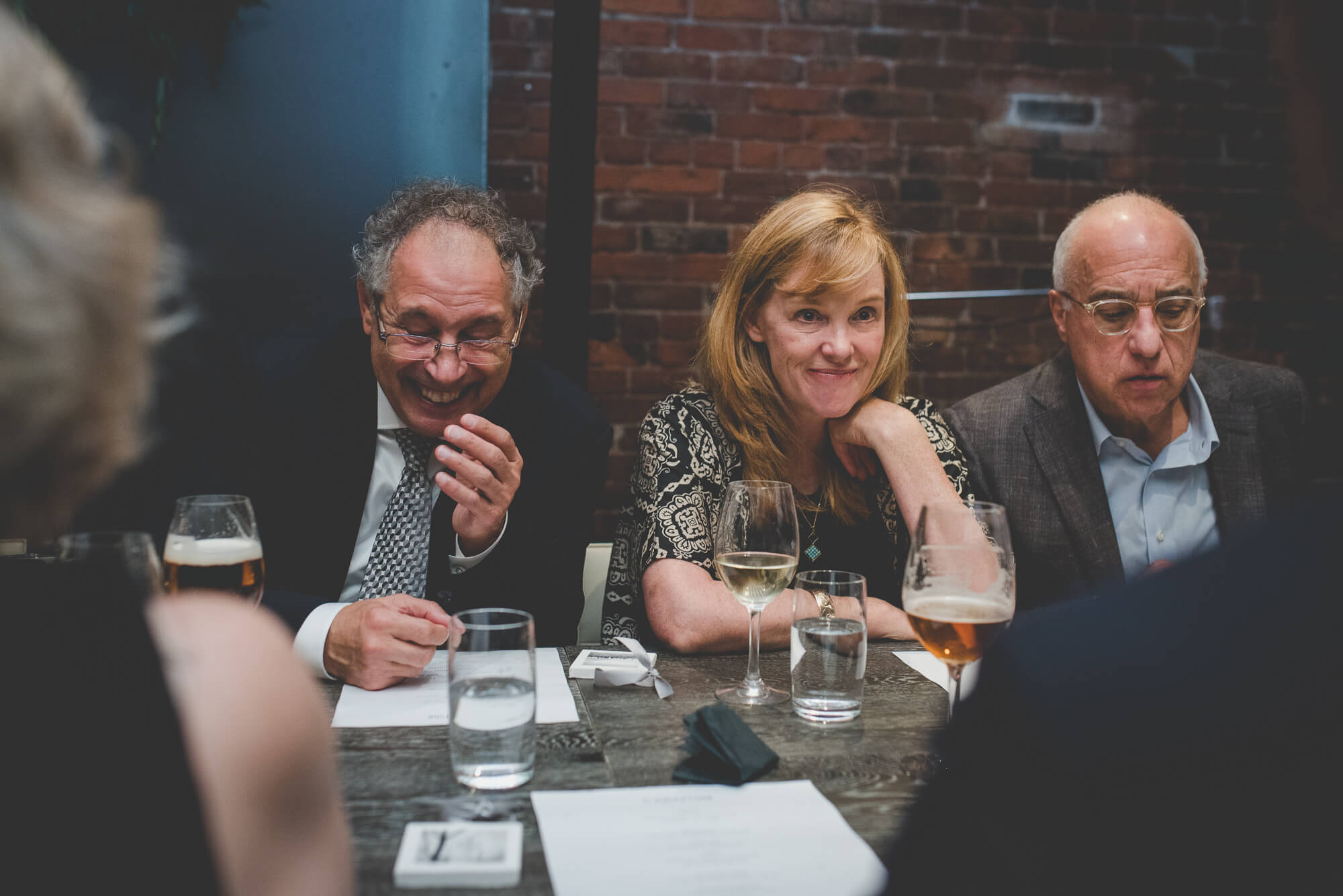 guests laughing over beer and wine at wedding reception