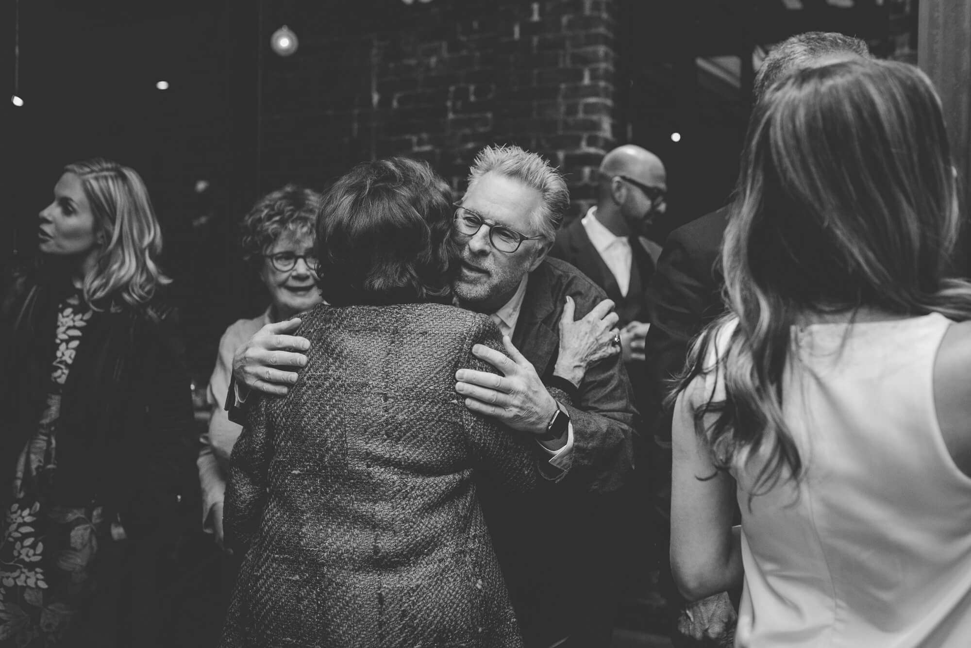guests hugging at industrial wedding reception in Gastown