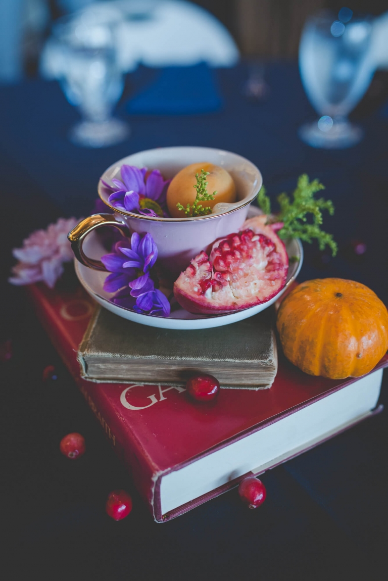 whimsical wedding centerpiece with vintage books, a teacup, purple flowers, and fruit