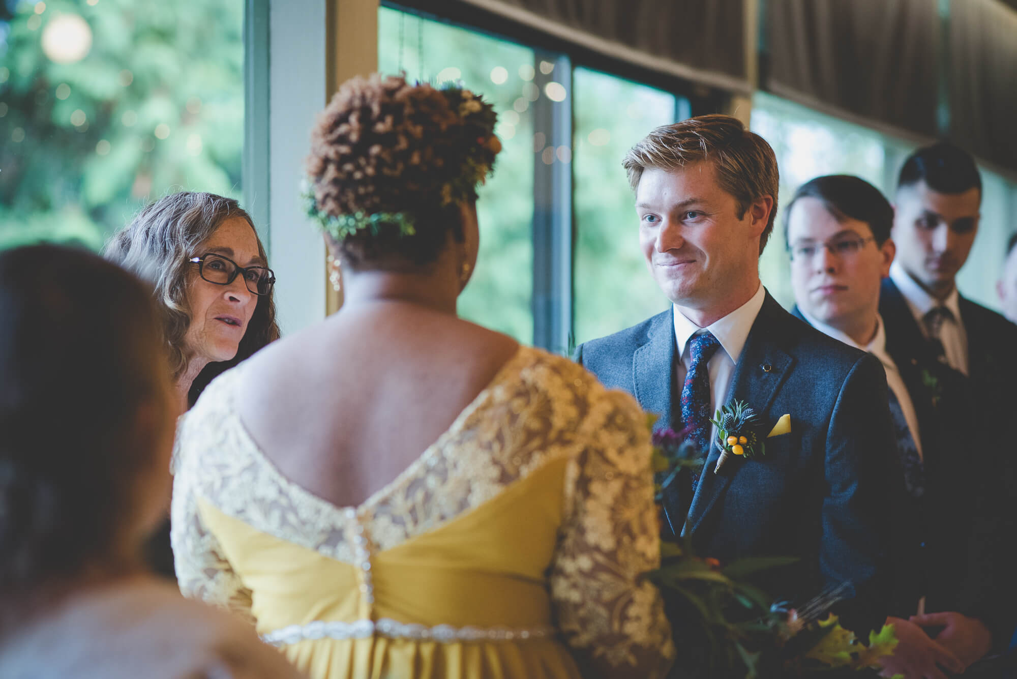 groom smiling at bride in yellow wedding dress during wedding vows