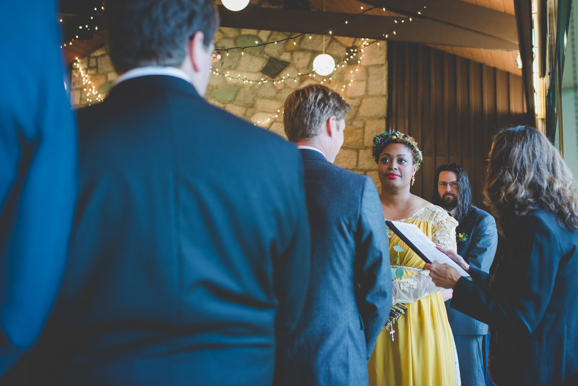 bride in beautiful yellow wedding dress with succulent headpiece looking at groom during wedding vows