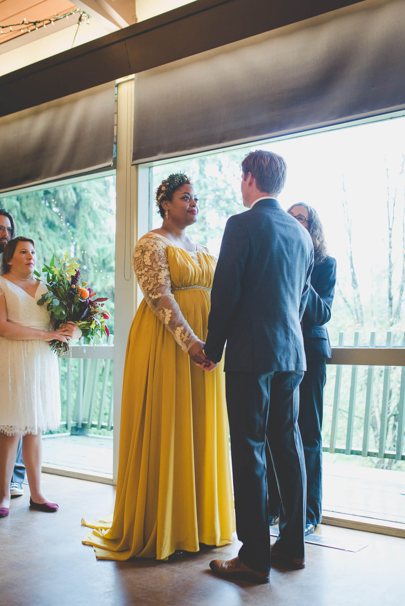 bride in flowing yellow wedding dress with lace sleeves and succulent headpiece during wedding ceremony