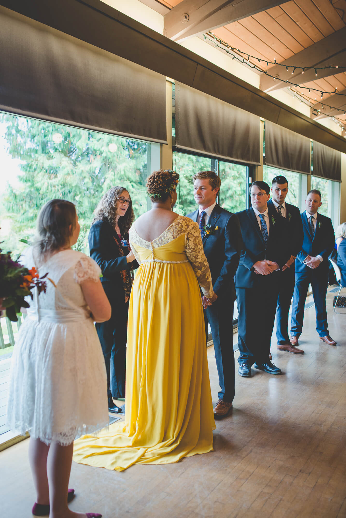 groom looking at bride in yellow flowing wedding dress with lace sleeves during wedding at Centennial Lodge in New Westminster