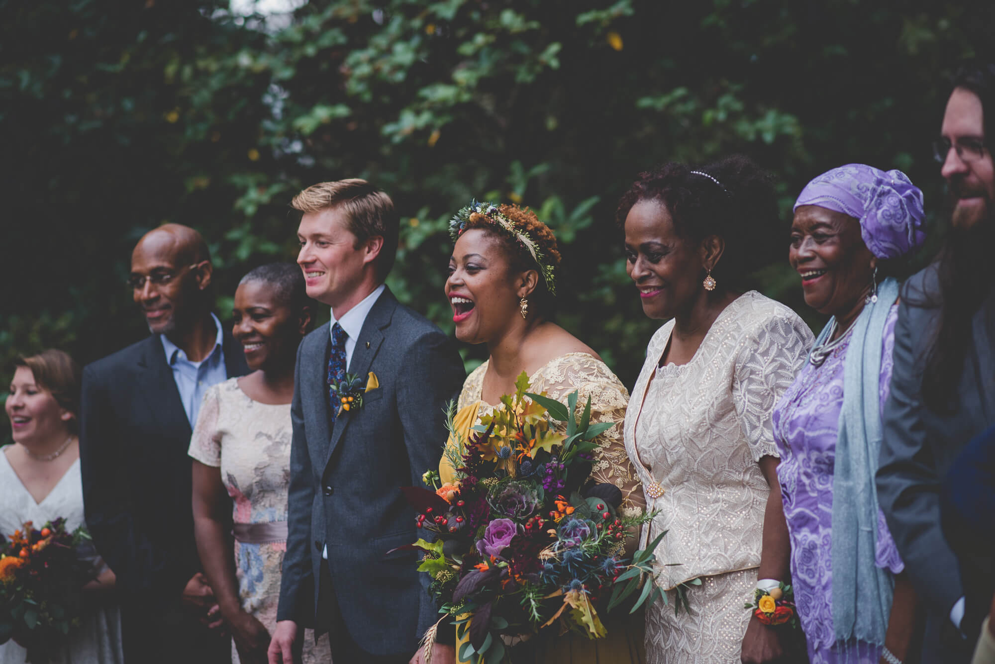 bride and groom laughing with bride's family during family formals at wedding