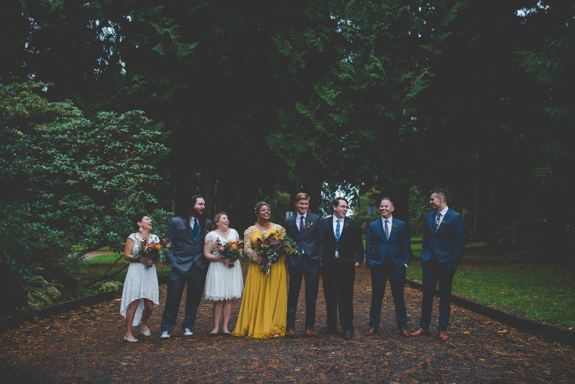 bride in flowing yellow wedding dress with long lace sleeves laughing with wedding party in Queens Park in New Westminster