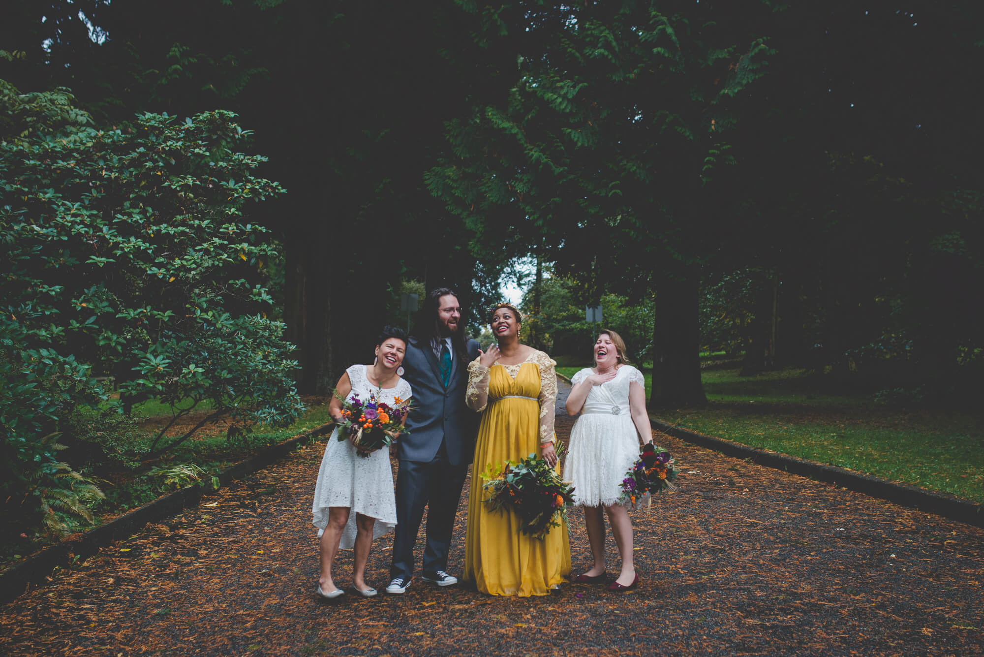 bride in beautiful yellow wedding dress and succulent bouquet laughs with wedding party at Centennial Lodge in New Westminster