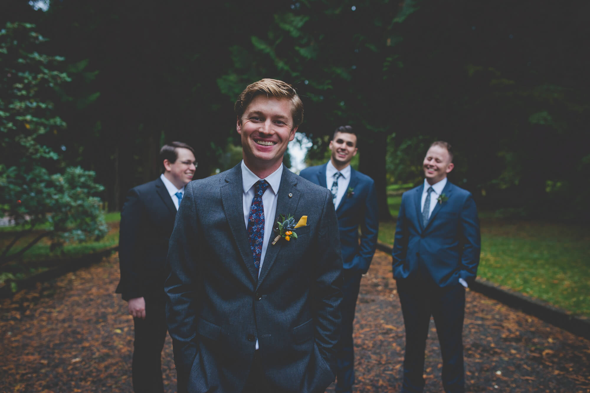 groom and groomsmen laugh together during wedding party portraits