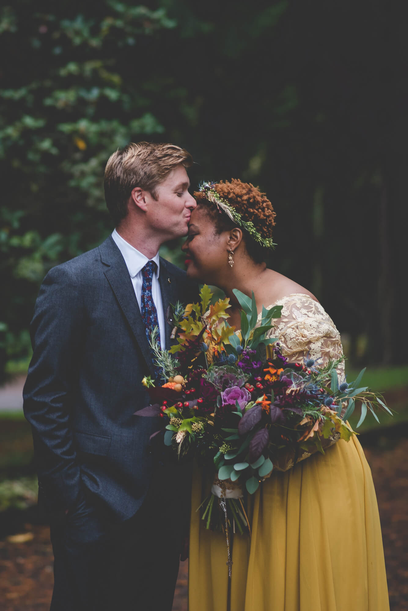 groom kissing bride's forehead in yellow flowing wedding dress with succulent bouquet and flower crown