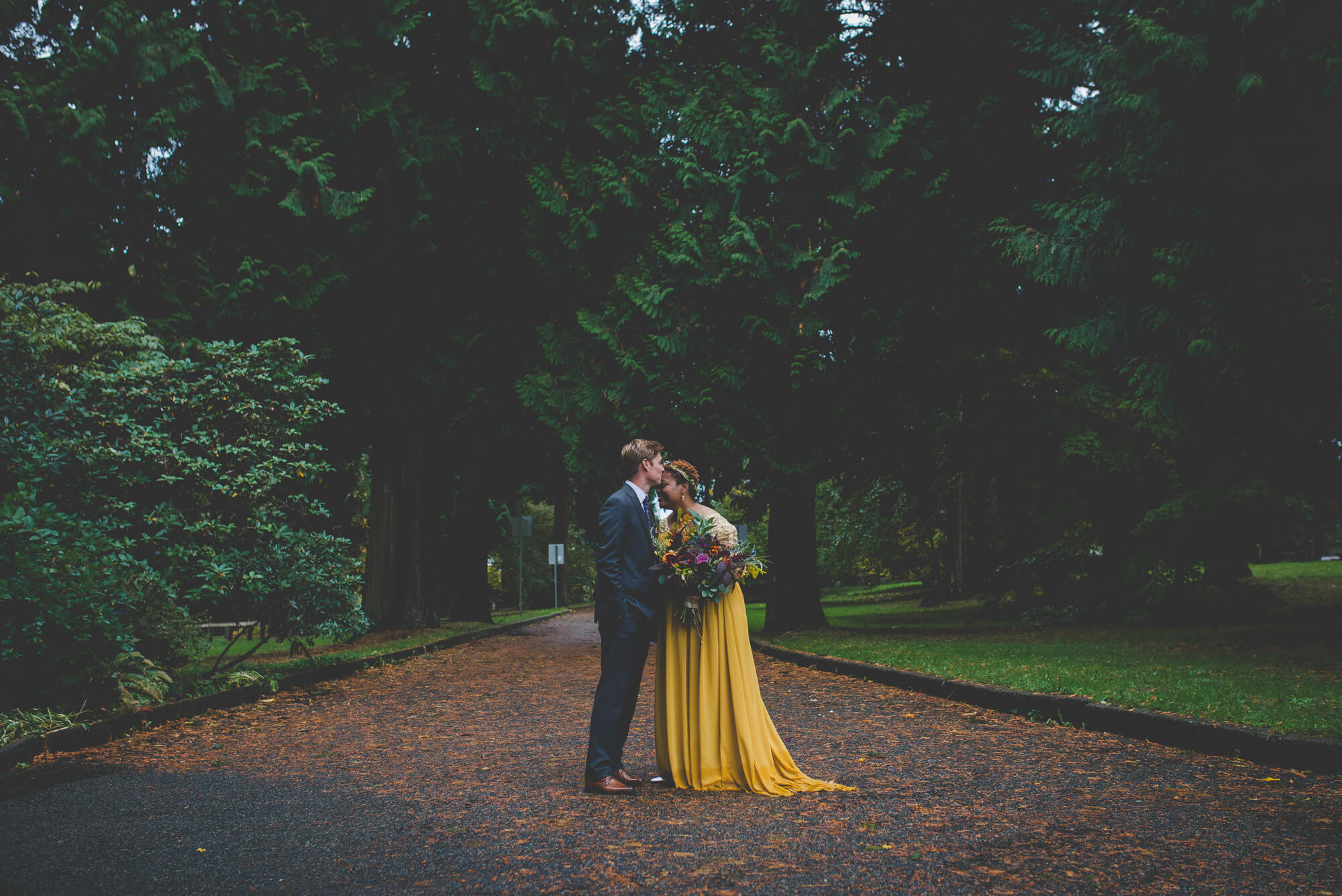 bride in flowing yellow wedding dress and succulent bouquet getting kiss on forehead from groom during wedding portraits