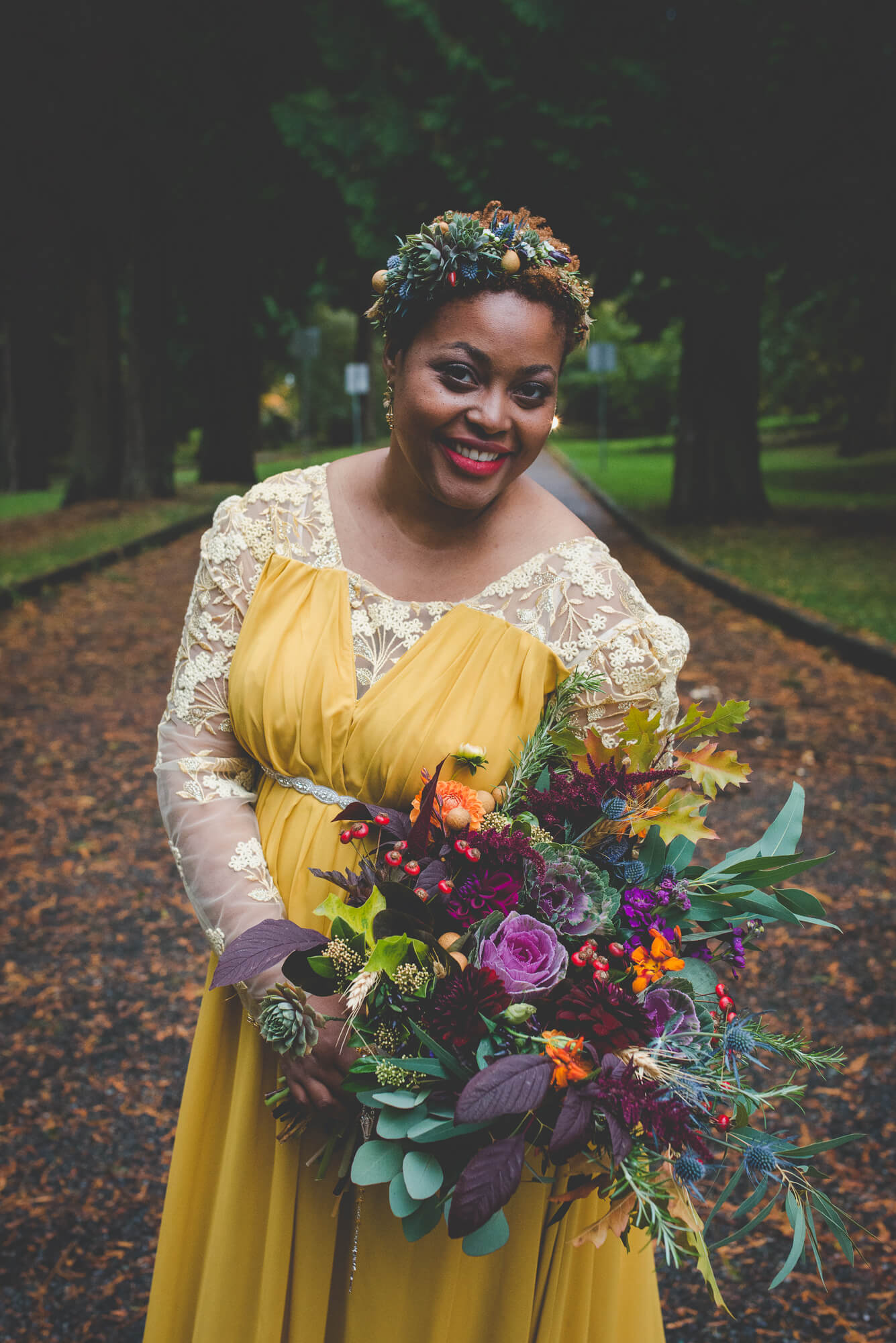 bride in yellow flowing wedding dress with long lace sleeves and succulent headpiece and bouquet