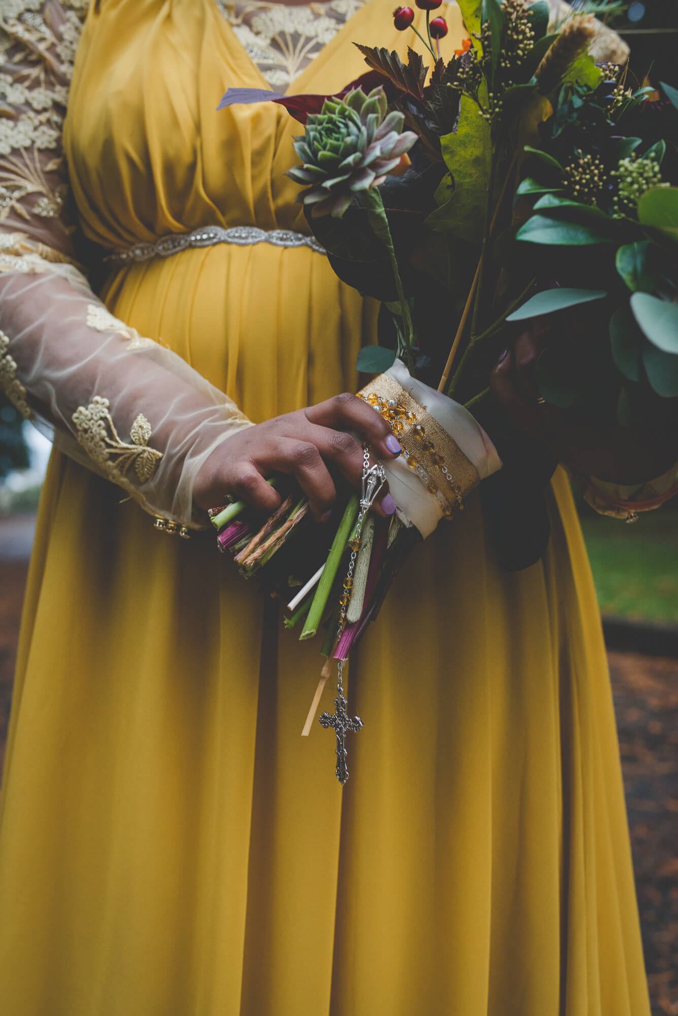 bride in flowing yellow wedding dress holding rosary with succulent bouquet