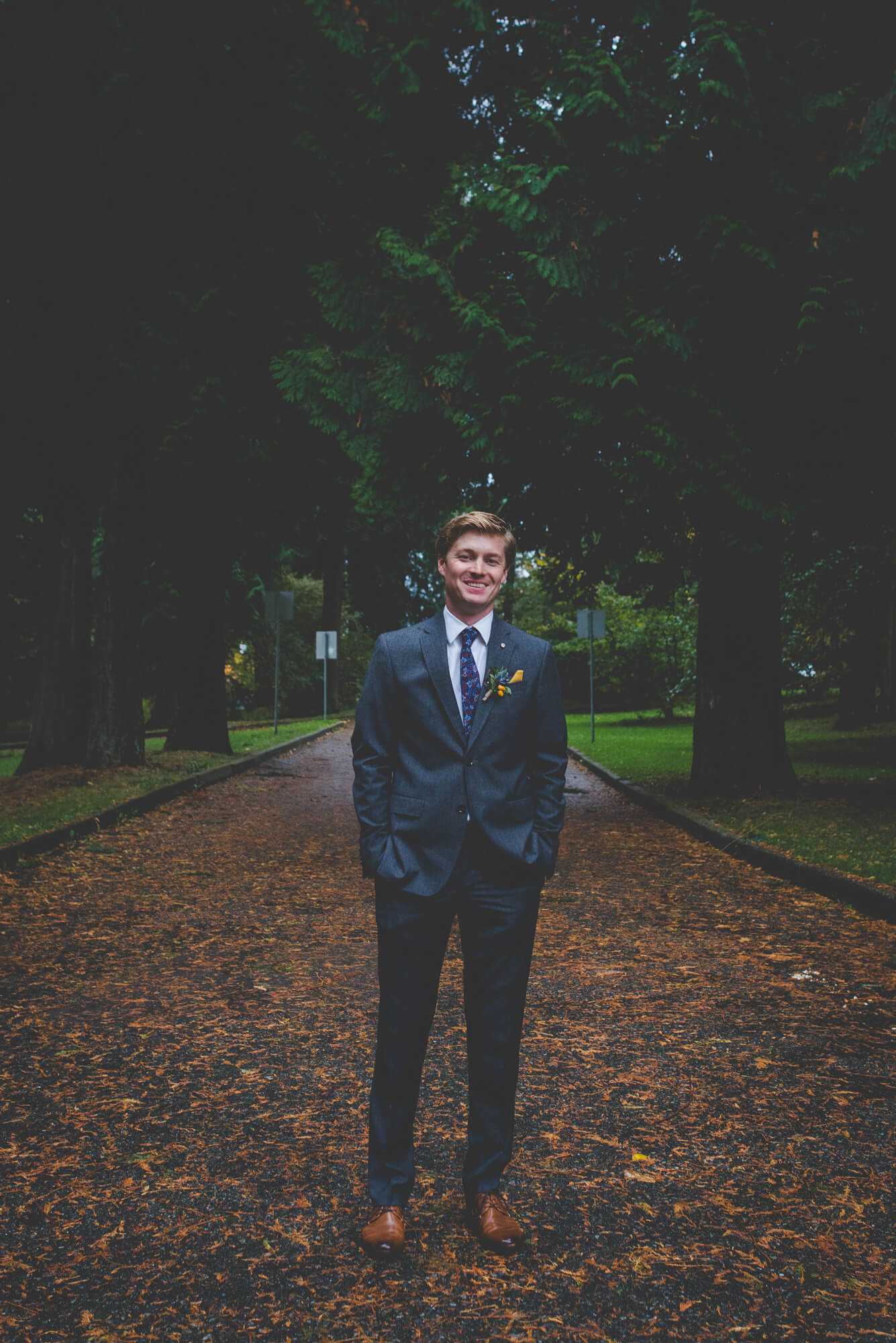 groom smiling during wedding portraits in Queens Park