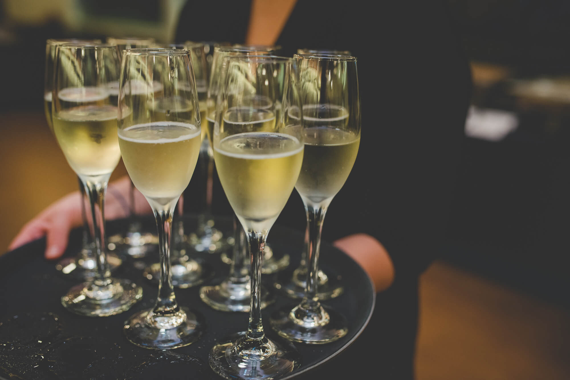 server passing around tray of champagne for toasts at wedding reception in New Westminster