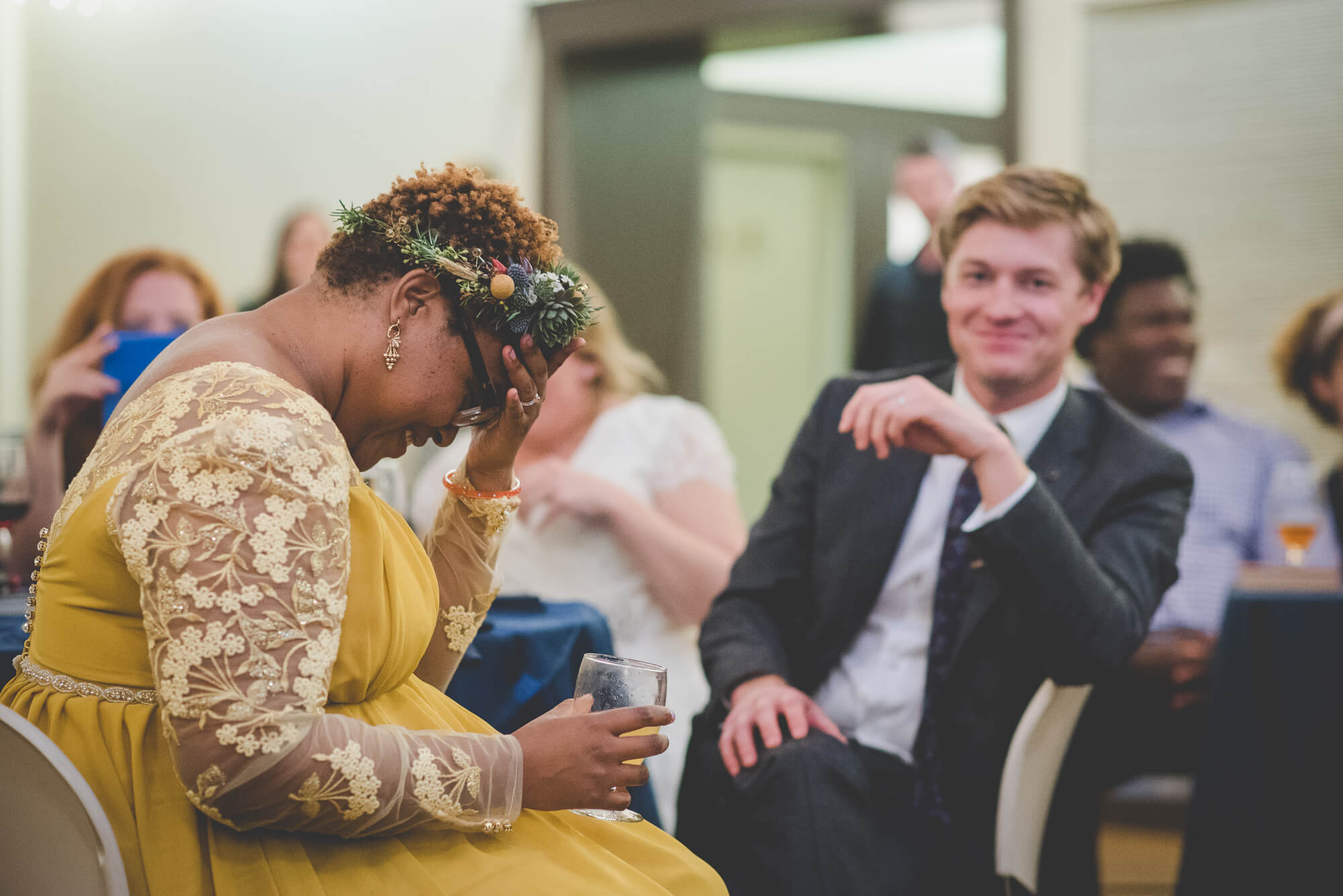 bride in yellow wedding dress with long lace sleeves and succulent headpiece laughing during toasts at wedding reception