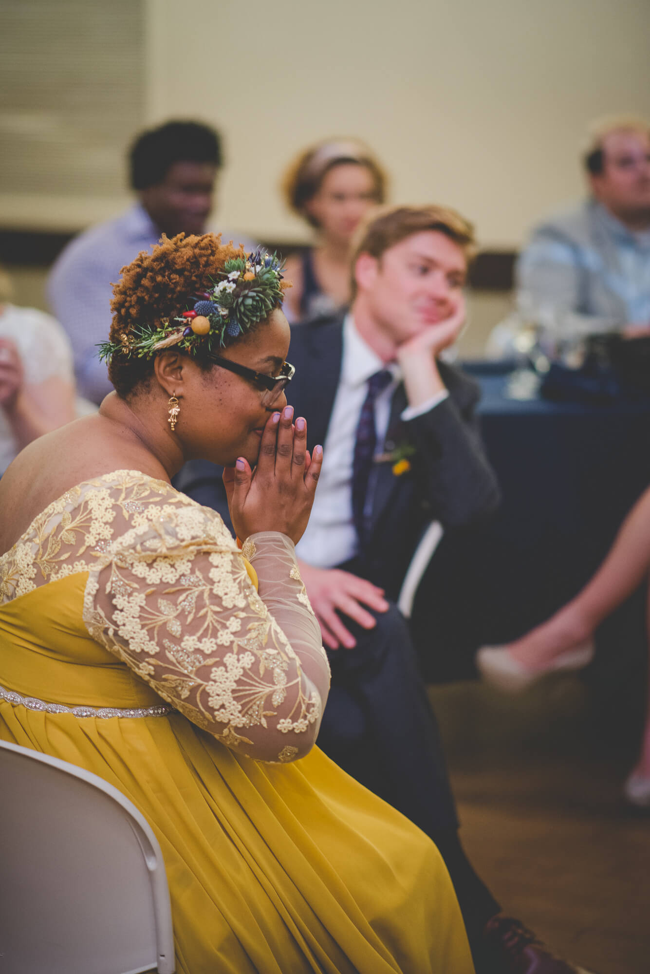 bride in yellow wedding dress with long lace sleeves and succulent flower crown quietly listening to guest singing during toasts