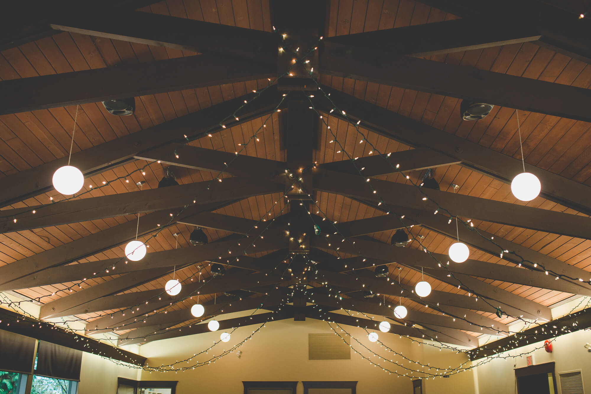 twinkle lights strung from wooden beam ceiling at wedding reception at Centennial Lodge
