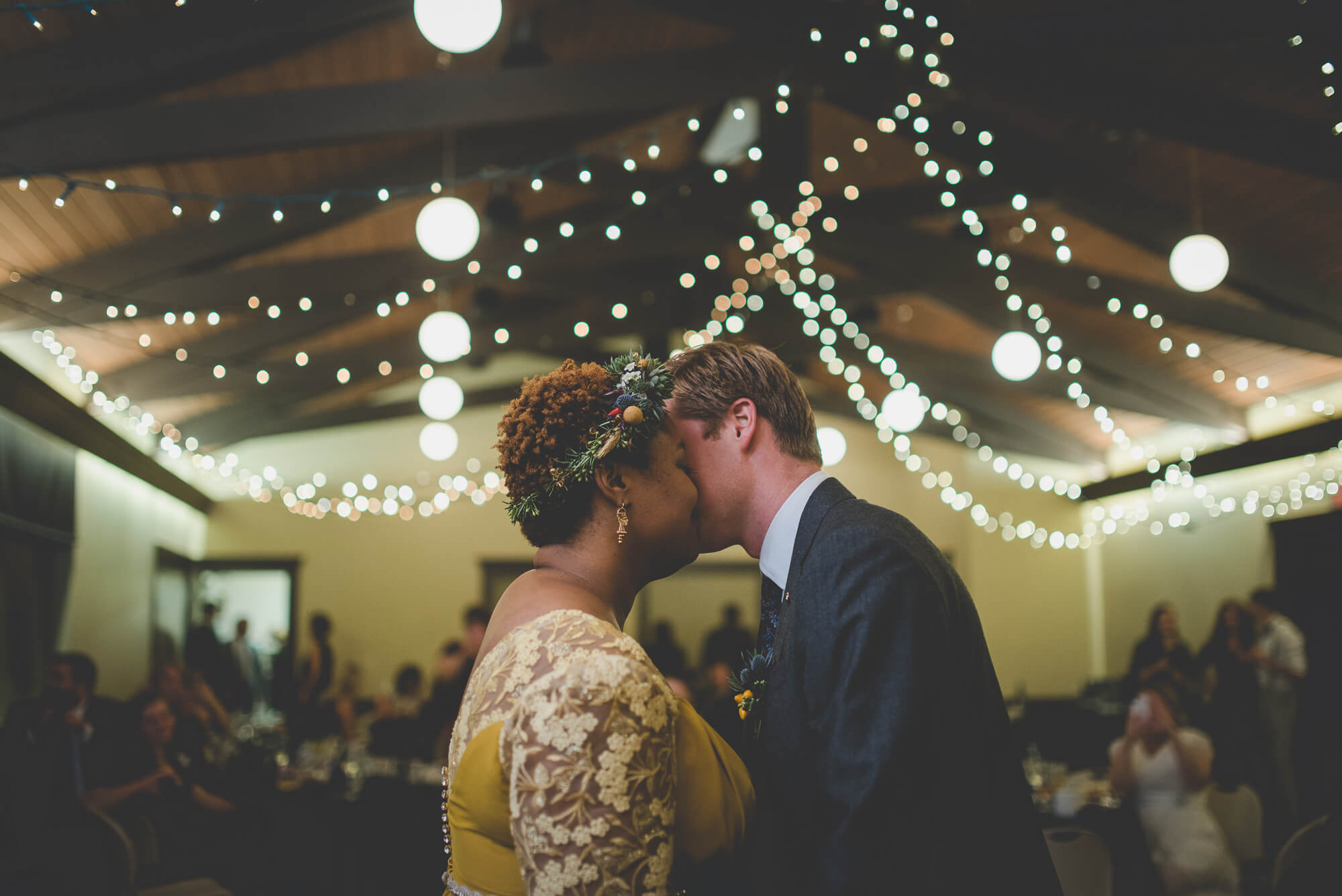 bride and groom dancing cheek to cheek during first dance with twinkle lights hanging from wooden ceiling beams