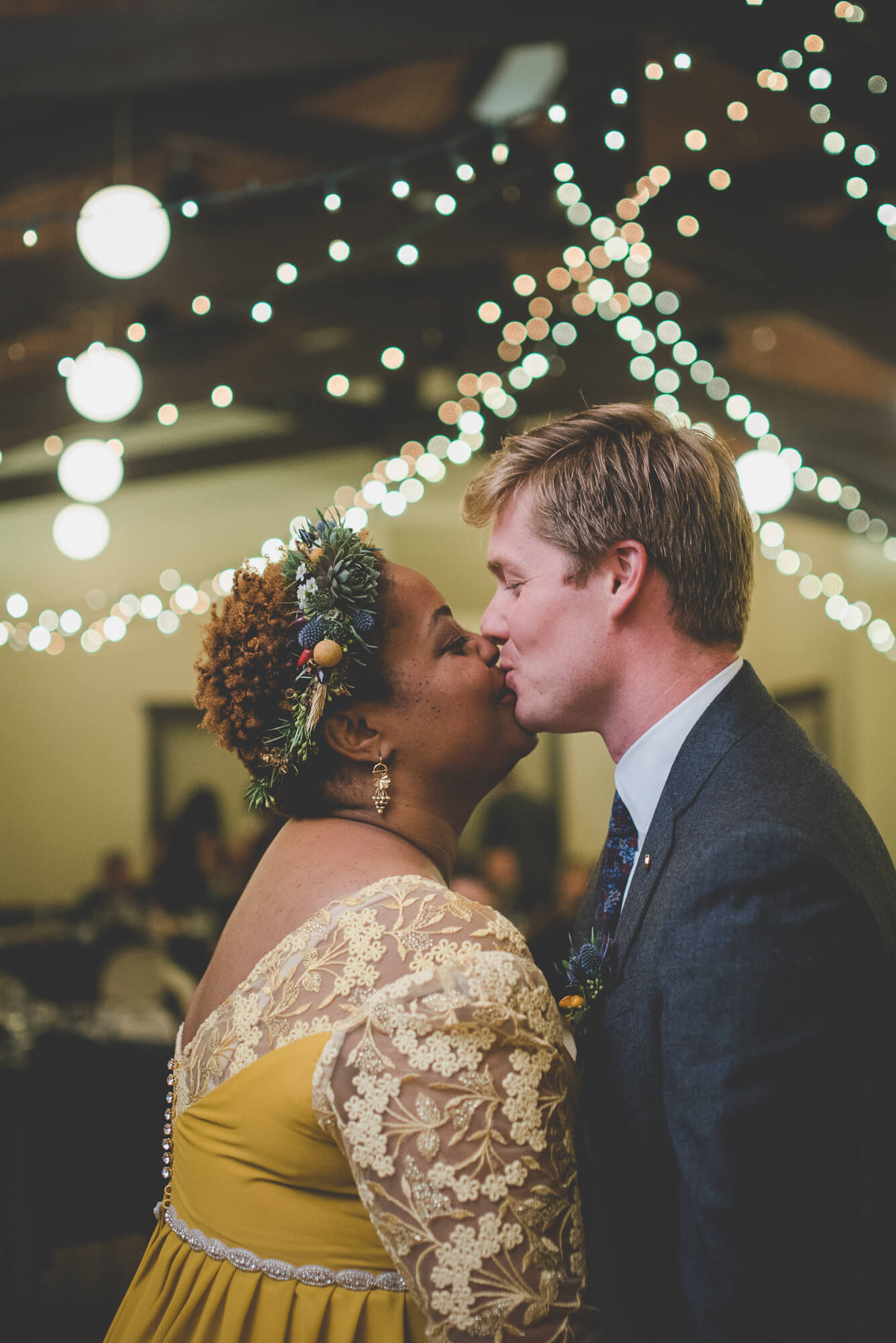bride in yellow wedding dress with lace sleeves kisses groom during first dance with twinkle lights hanging from wooden ceiling beams