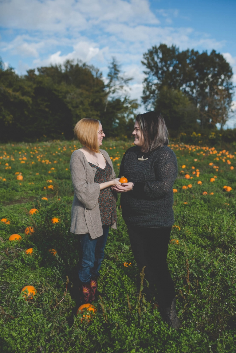 LGBT couple holding tiny pumpkin at pumpkin patch maternity session in Richmond