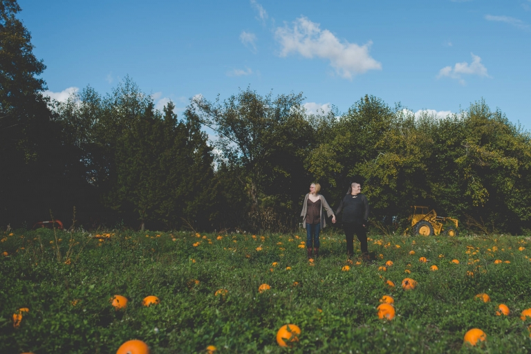 same sex couple in field of pumpkins during maternity shoot