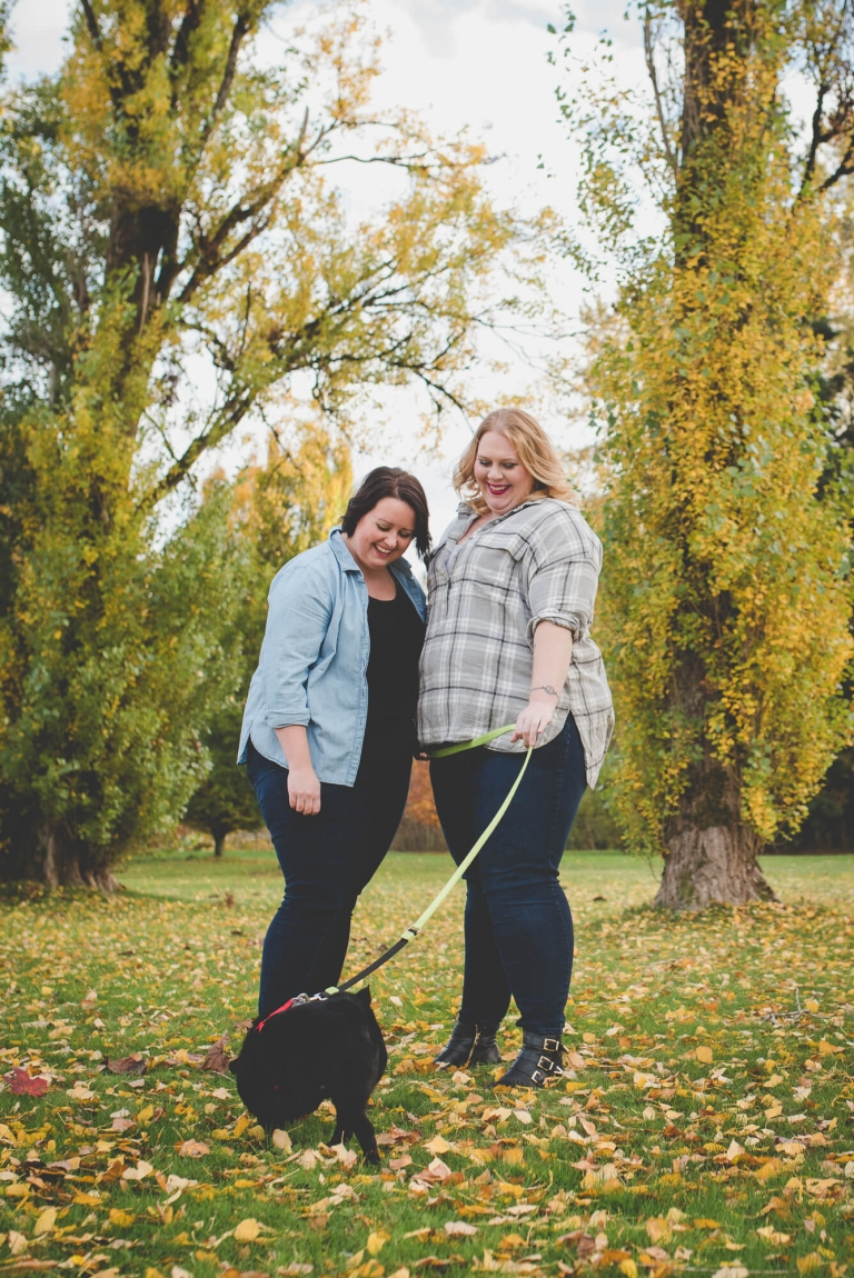 same sex couple laugh at their black pug puppy in autumn leaves in East Vancouver | Queen Elizabeth Park engagement | Vancouver LGBT wedding photographer