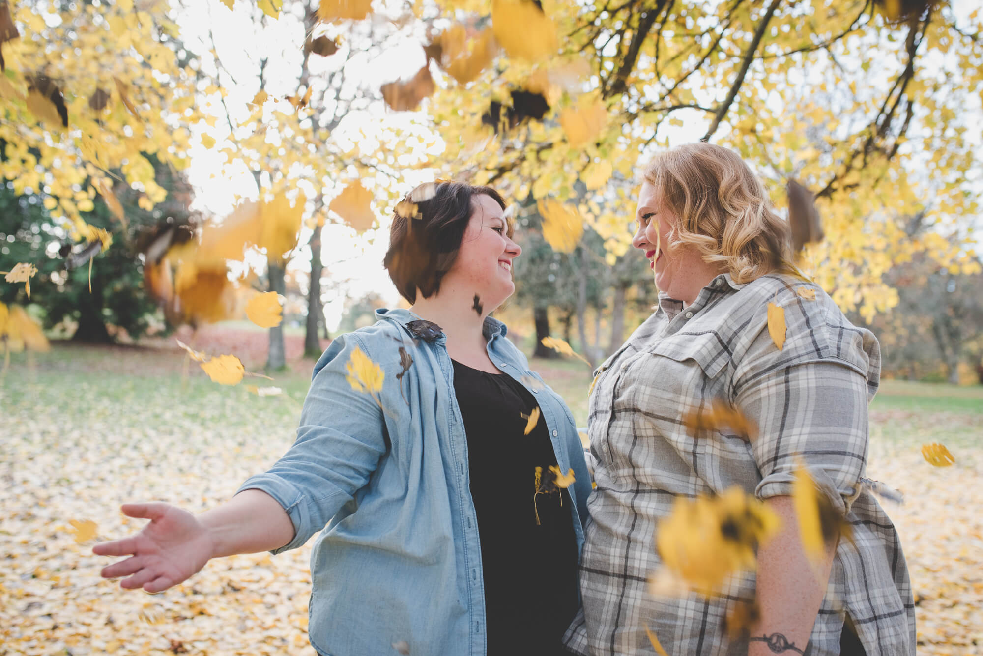 same sex couple throw yellow leaves in the air | fall engagement at Queen Elizabeth Park | Vancouver same-sex wedding photographer