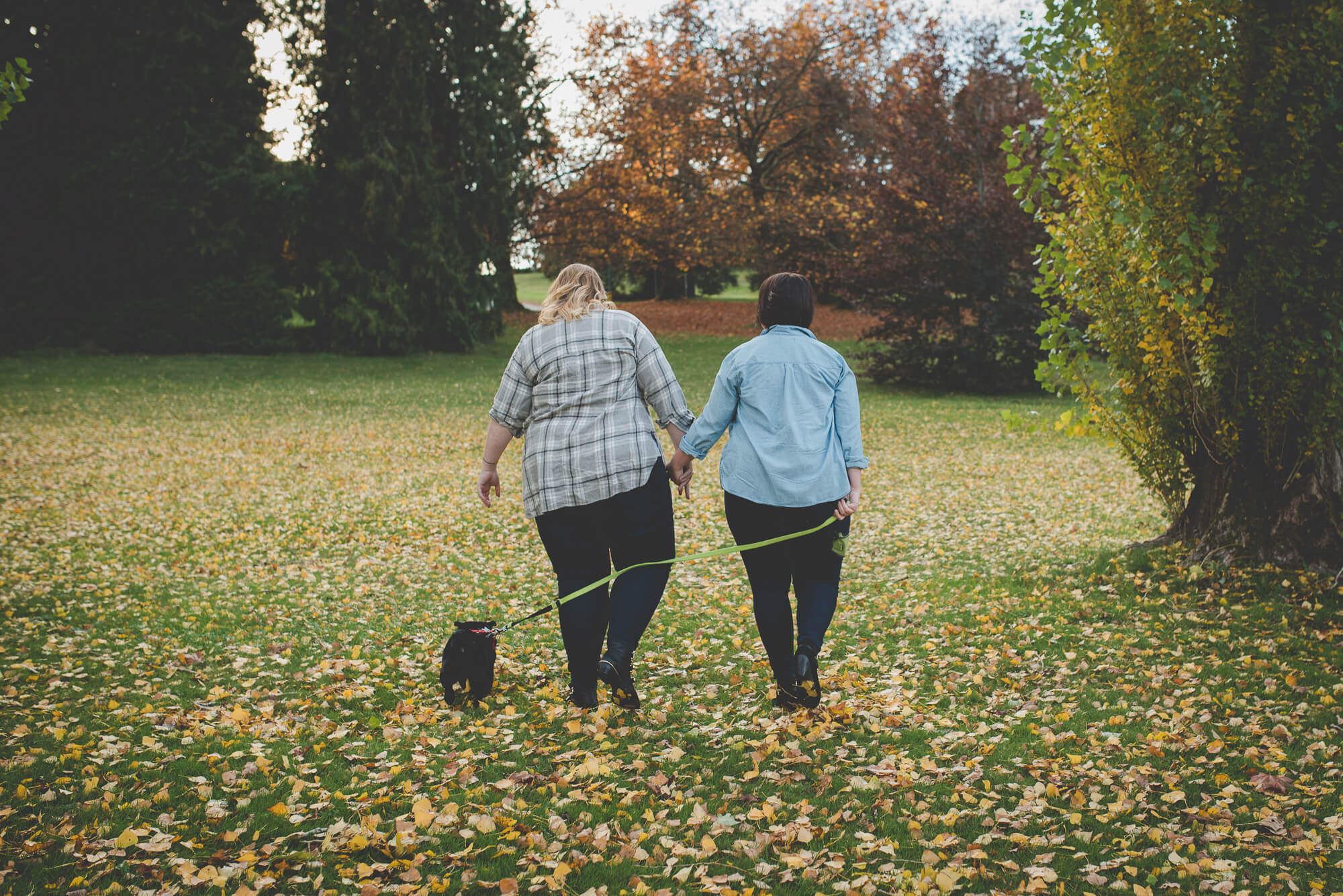 lesbian couple walks in the leaves with puppy | Queen Elizabeth Park engagement | Vancouver LGBT wedding photographer