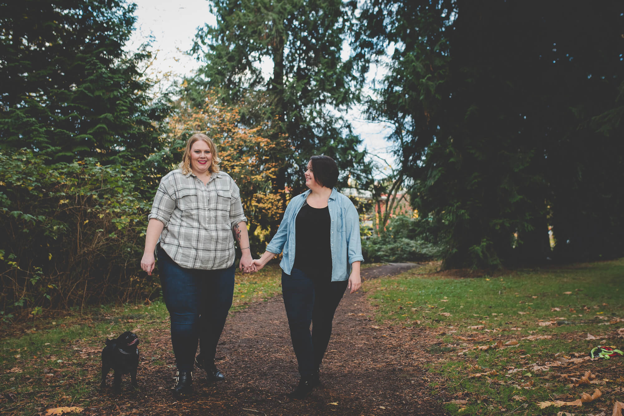 lesbian couple walk together with their black pug in the forest | QE Park autumn engagement | Vancouver lesbian wedding photographer
