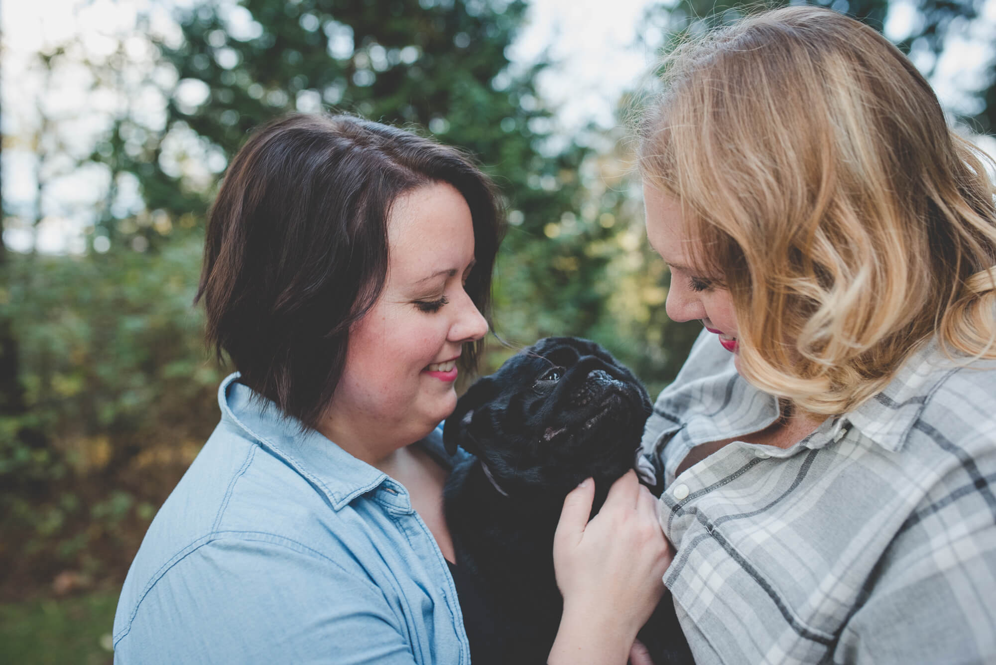 same sex couple smile and hug their black pug puppy | Queen Elizabeth Park engagement | Vancouver LGBT wedding photographer