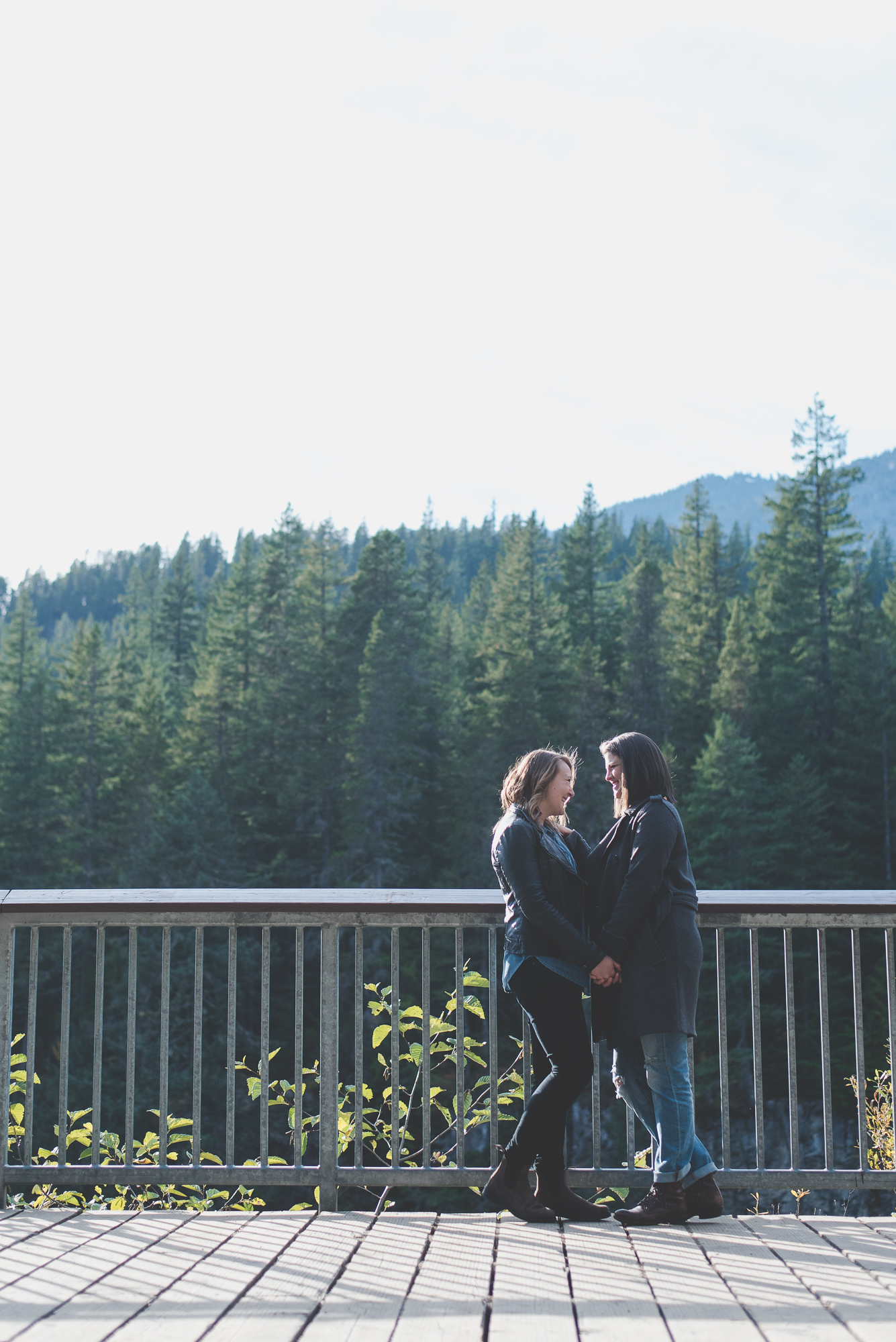 female partners holding hands and laughing together at Brandywine Falls lookout in Whistler