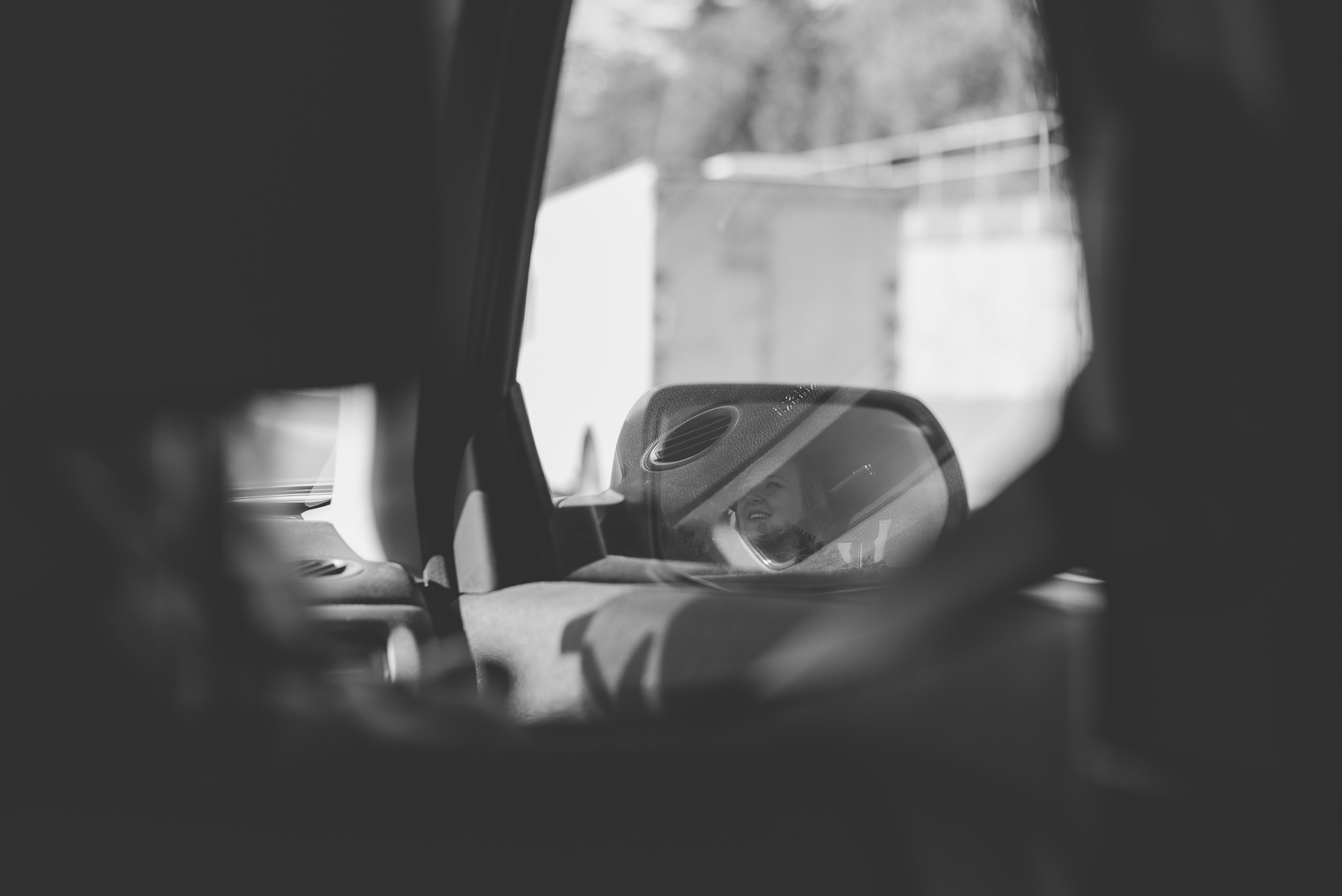 reflection of woman smiling in side mirror of car