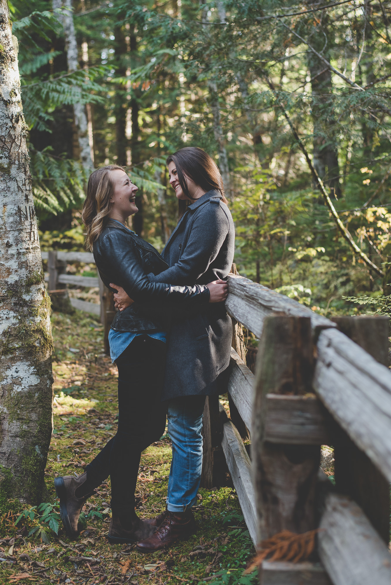 two girlfriends leaning against wooden fence and laughing