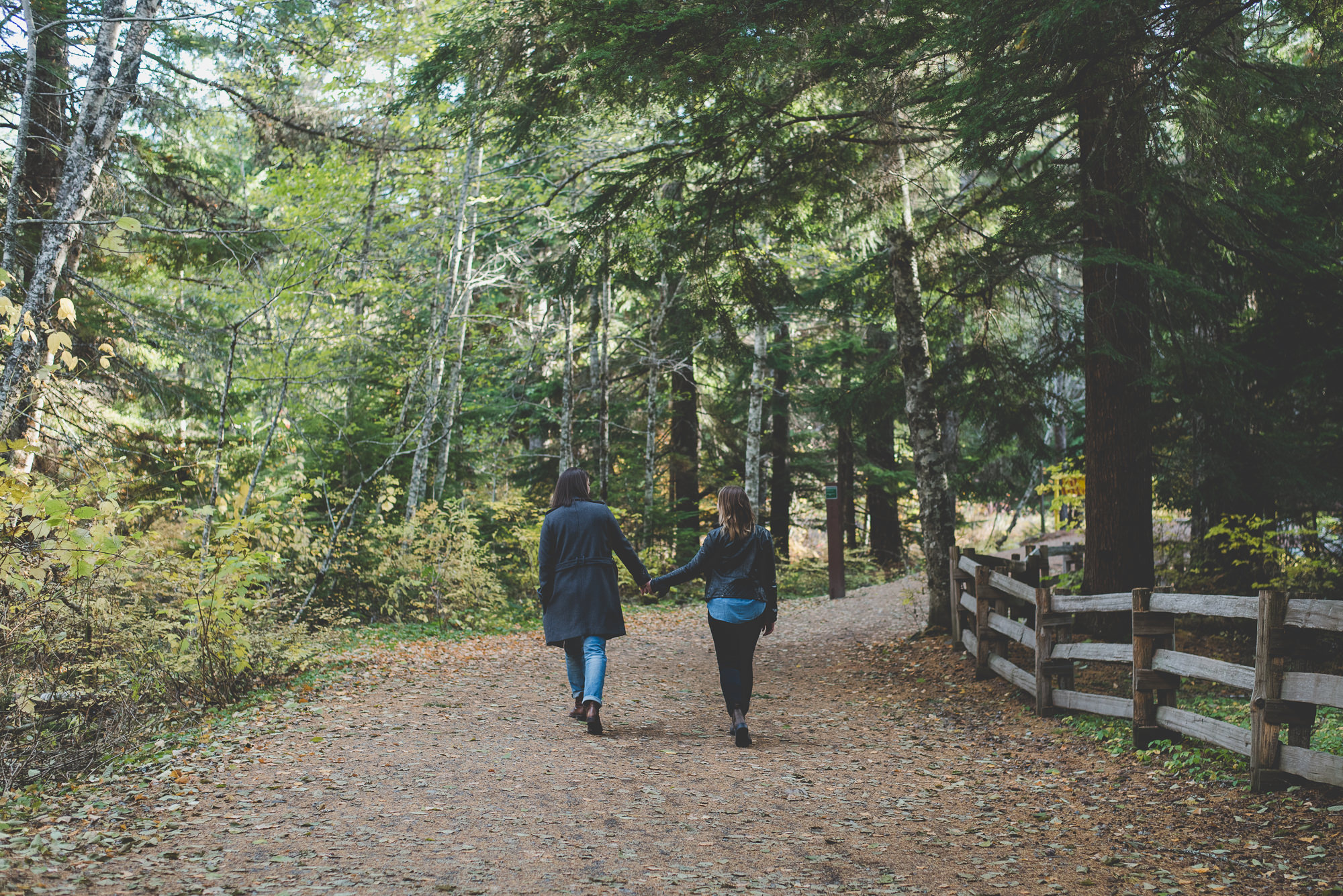 lesbian couple holding hands and walking away down a path