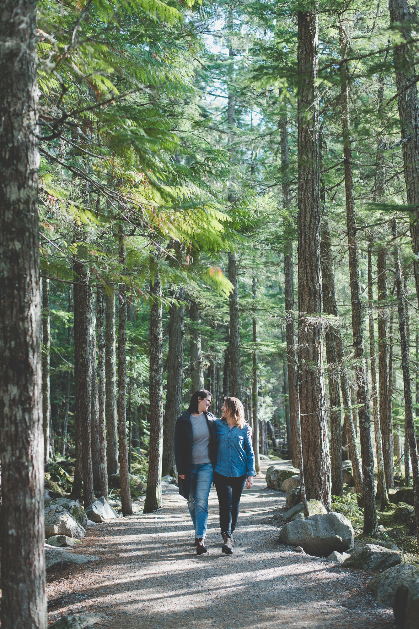 lesbian couple walking together down tree lined path at Brandywine Falls engagement session
