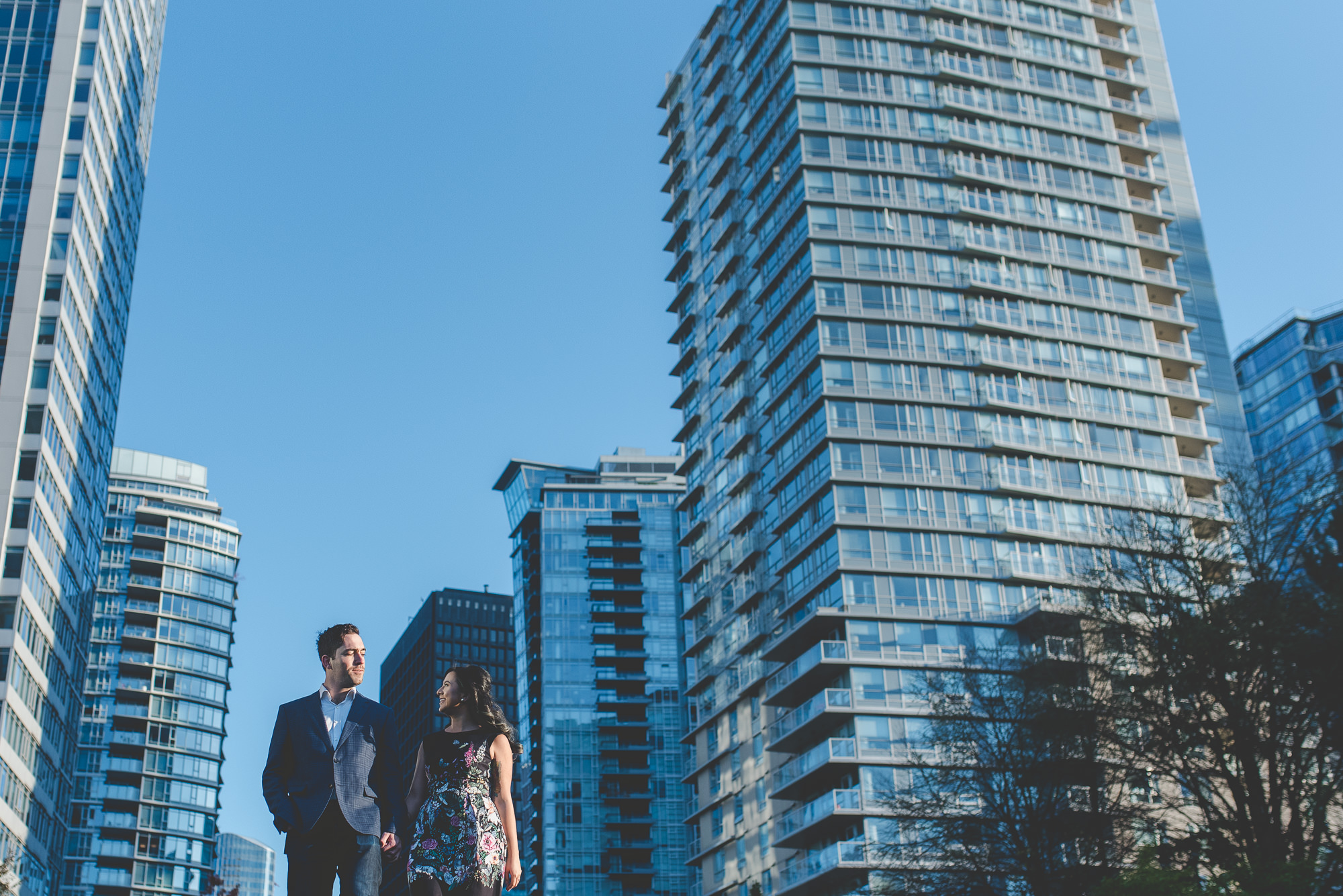 couple looking at each other while walking with Vancouver skyline in background