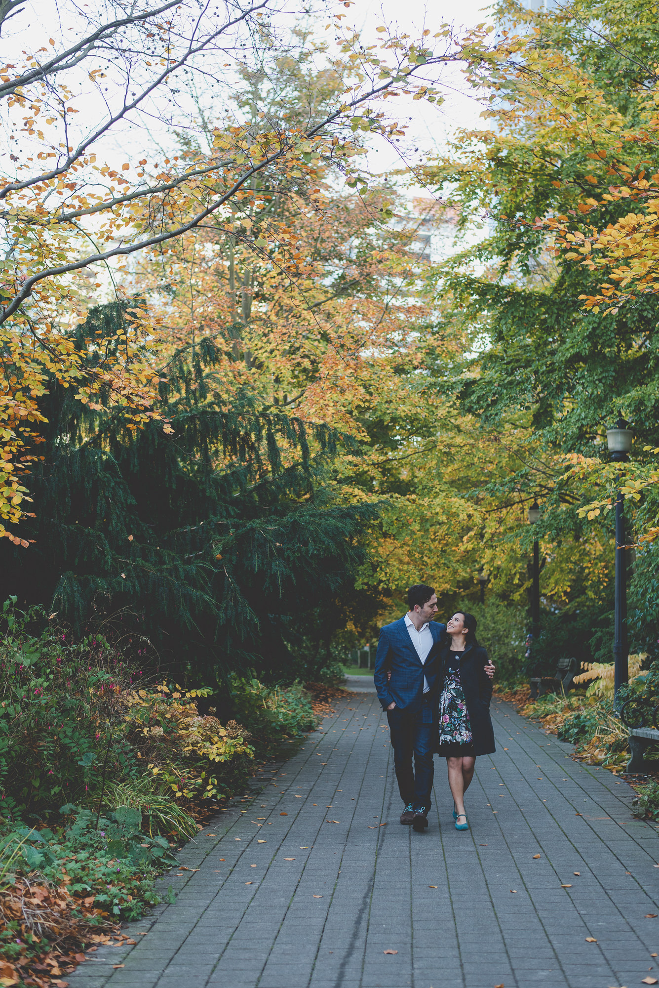 couple walking down path between autumn trees with arms around each other