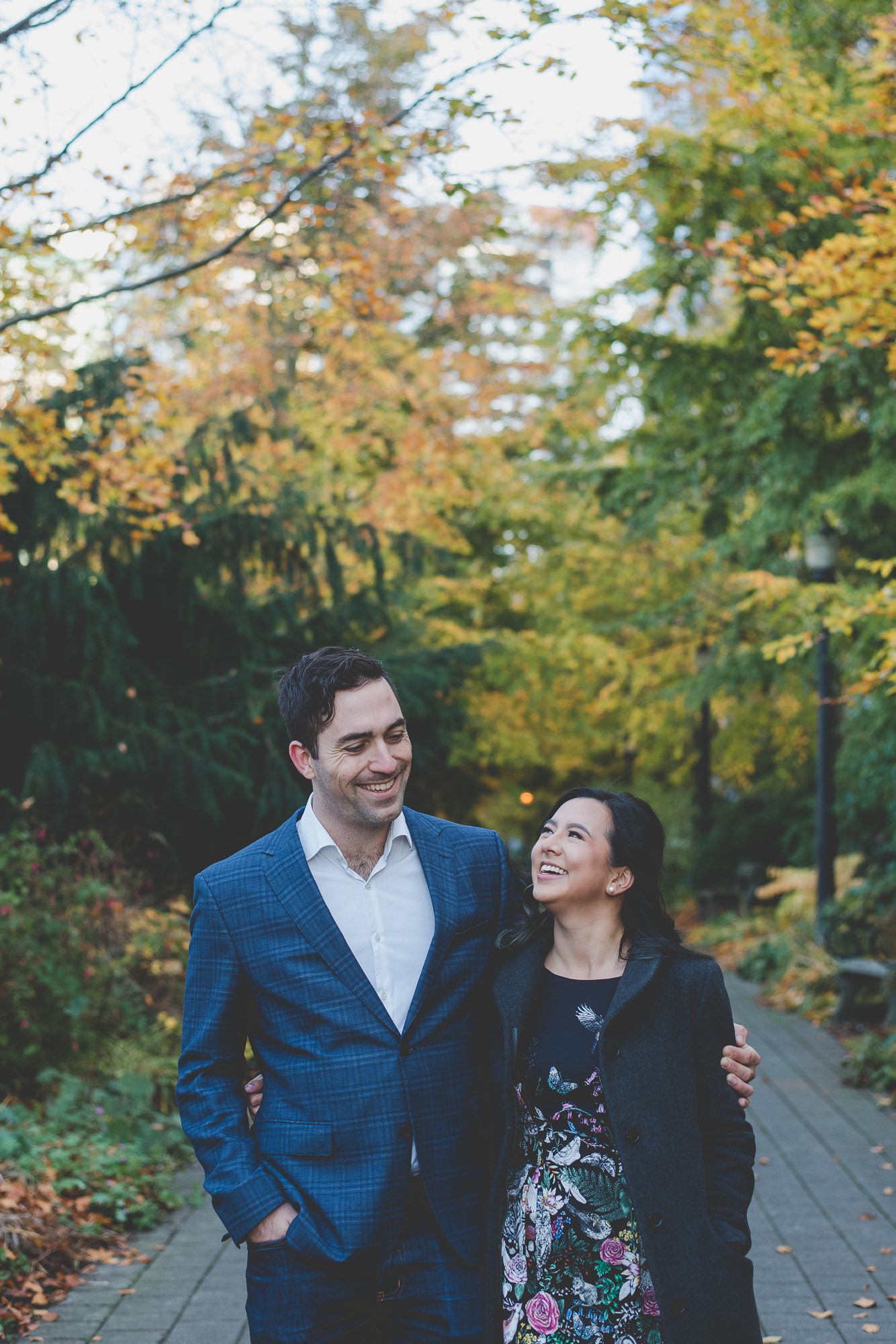 couple laughing together while walking between autumn trees